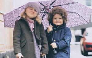 Lapset sateenvarjon alla kumppareissaan.
