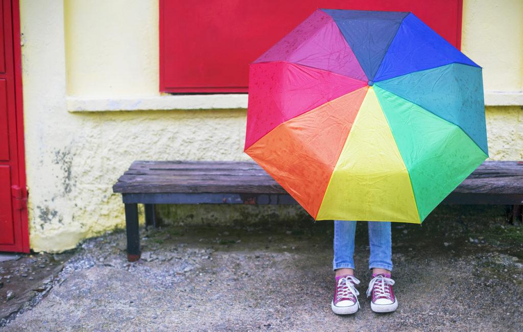 Lapsi piilossa sateenvarjon takana.