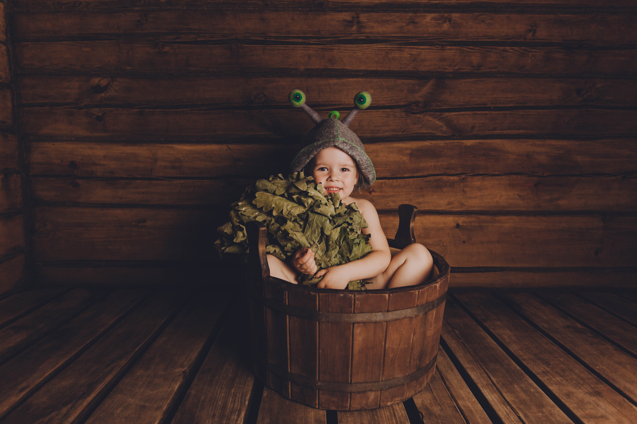 Lapsi saunassa? Pieni lapsi istuu paljussa hattu päässä ja vihta sylissä.