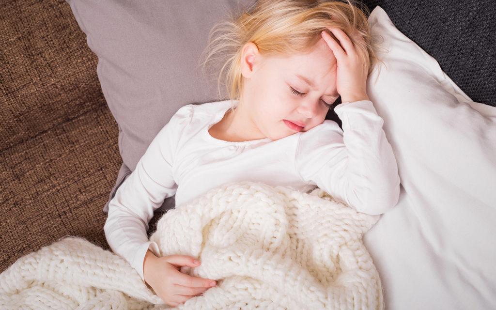 tarttuuko koronavirus lapsiin? Tyttö pitelee kivistävää päätään.