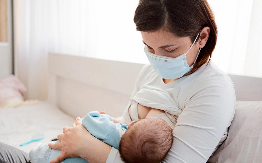 Koronavirusposiviinen äiti imettää lastaan kasvomaski kasvoilla.