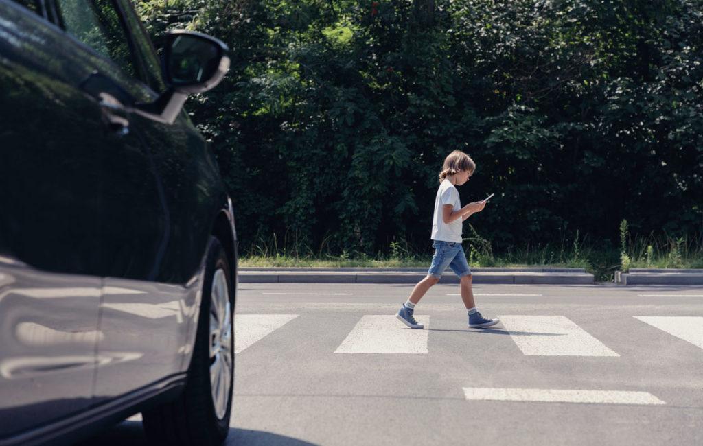 Suojatien ylittäminen ripeästi voi unohtua, jos lapsen huomio on kiinnittynyt puhelimeen.