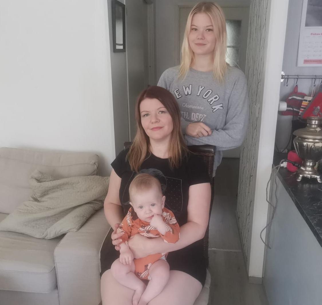 Mari istuu kuopus sylissään. Taustalla seisoo Kia, Marin lapsenlapsi vatsassaan.