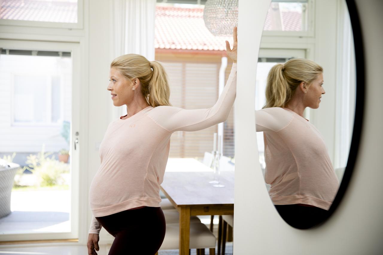 Venytysliikkeitä raskauteen: olka-hartia seinää vasten