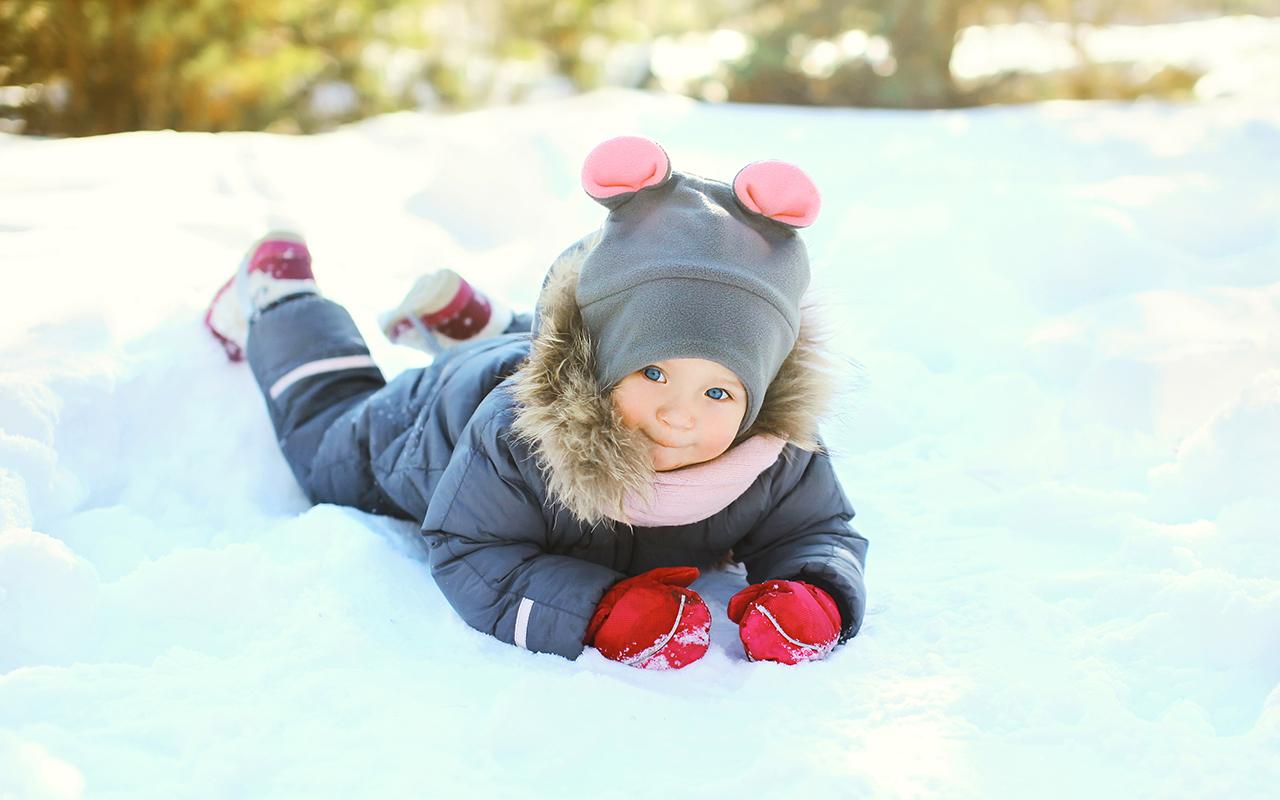Reima Weather app -sovellus lupaa helpottaa pukemisrumbaa. Kuvassa pieni lapsi makoilee haalari päällä lumihangessa.